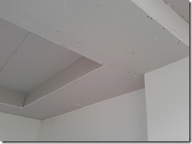 The dropped ceiling extends the width of the beam towards the centre of the room